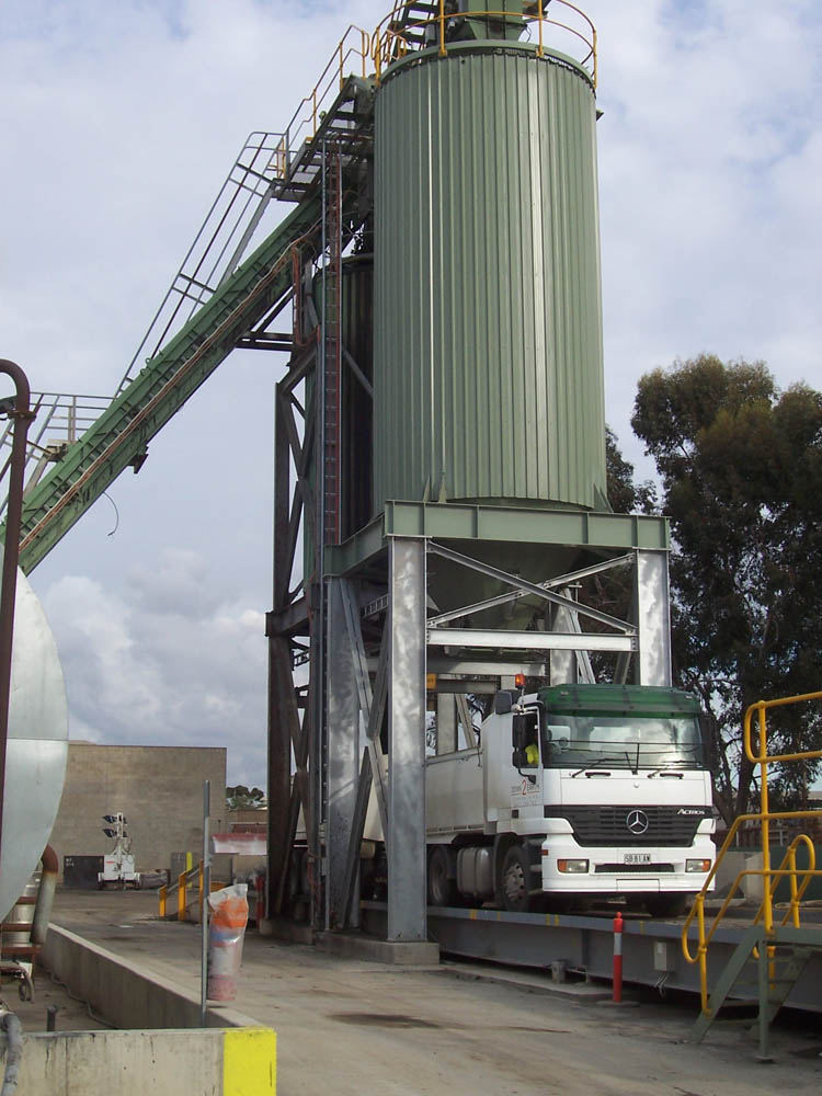 An image of a truck on a silo and slat conveyor